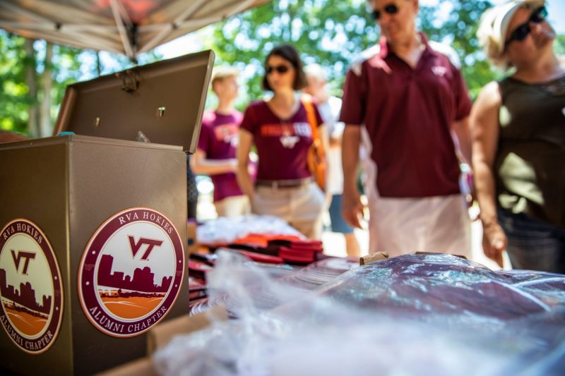 Outside, people in maroon Virginia Tech shirts look at a table of Hokie items, including magnets with the Richmond Hokies logo.